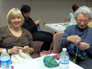 Darlene Pawlicki (left) teaches knitting to a new student.